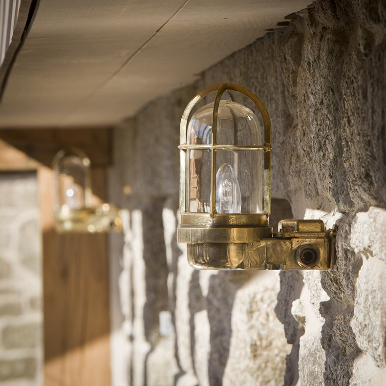 Brass nautical bulkhead light in hallway